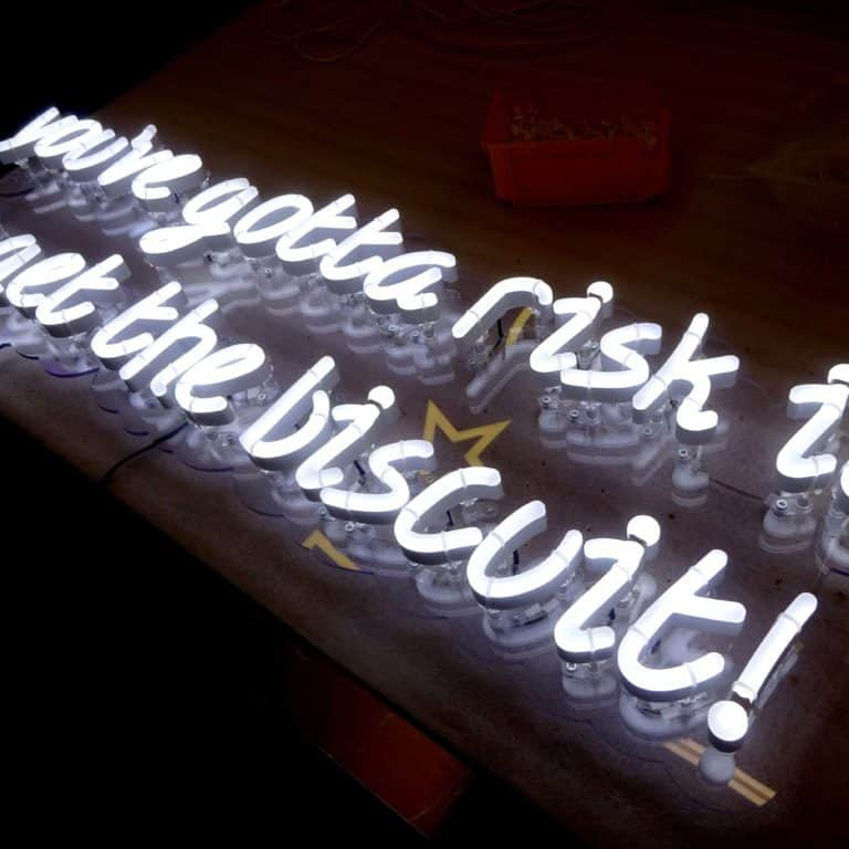 Youve gotta risk it to get the biscuit white faux neon phrase display