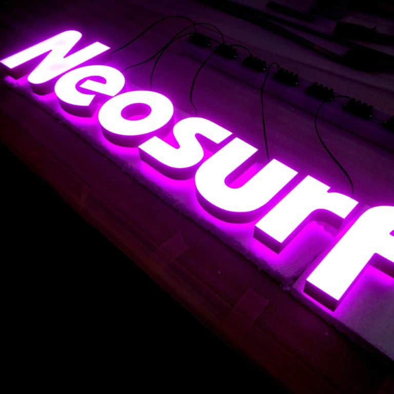 Pink illuminated neon sign reading 'Neosurf'. Storefront and weather resistant faux neon signs for signmaking and merchandising.