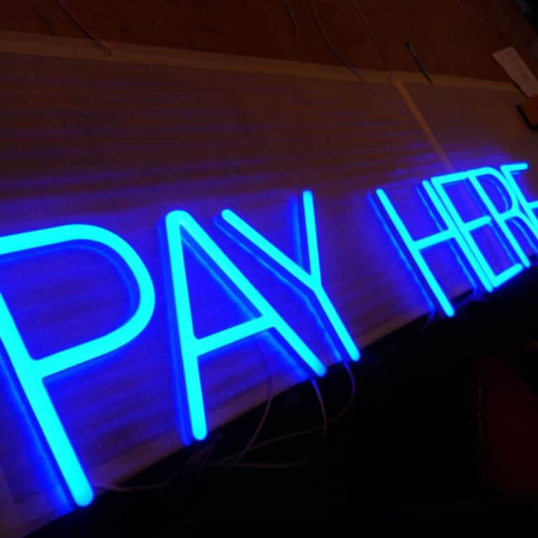 Faux Neon 'Pay Here' shop sign for bars and counters. Artificial neon backed with clear acrylic with energy efficient LED lighting.